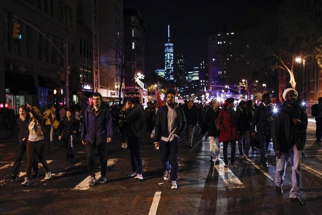 Protesters shout slogans against the law as they march on the street during a rally in New York, November 24, 2014, after the grand jury decided not to charge a Ferguson police officer in the deat ...
