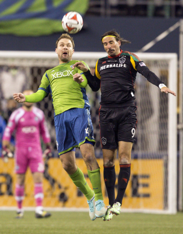 Seattle Sounders FC defender Chad Marshall (14) goes for a header with Los Angeles Galaxy midfielder Alan Gordon during the second half of the Western Conference Championship at CenturyLink Field, ...