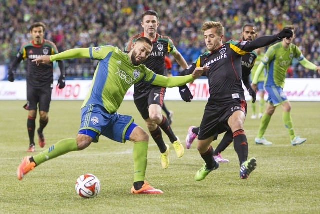 Seattle Sounders FC forward Clint Dempsey (2) gets off a shot despite the defense of Los Angeles Galaxy defender Robbie Rogers (14) during the second half of the Western Conference Championship at ...