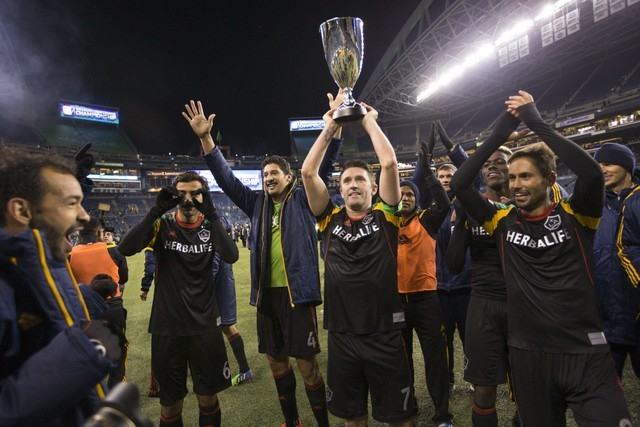 Los Angeles Galaxy forward Robbie Keane (7) holds the trophy after winning the Western Conference Championship against the Seattle Sounders FC at CenturyLink Field, Sunday, Nov. 30, 2014. (Joe Nic ...