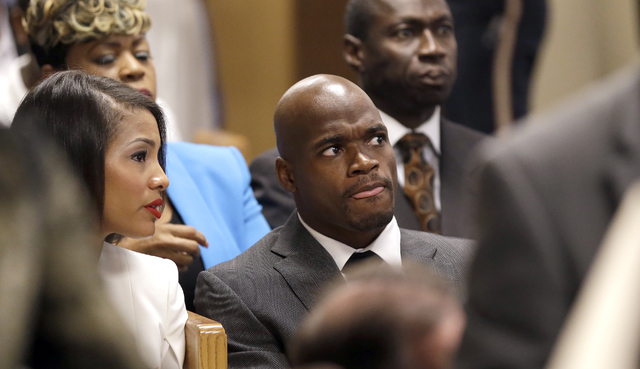 Minnesota Vikings running back Adrian Peterson, right, waits inside a courtroom with his wife Ashley Brown Peterson, left,  while making his first court appearance Wednesday, Oct. 8, 2014, in Conr ...