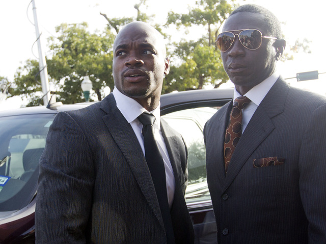 Minnesota Vikings running back Adrian Peterson, left,  arrives for court in Conroe, Texas Wednesday, Oct. 8, 2014. Peterson arrived to face a charge of felony child abuse for using a wooden switch ...