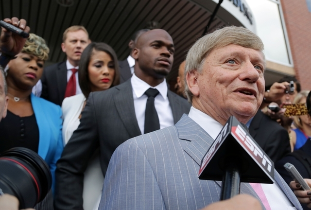Attorney Rusty Hardin talks to the media on behalf of his client,  Minnesota Vikings running back Adrian Peterson, behind Hardin, before leaving the Montgomery County courthouse in Conroe, Texas,  ...