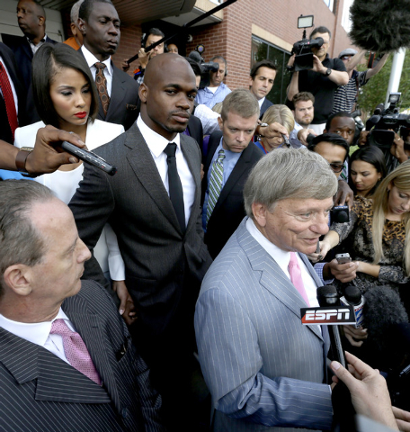 Minnesota Vikings running back Adrian Peterson, center, stands with his wife Ashley Brown Peterson, left, as they listen to Peterson's attorney Rusty Hardin, right, outside the courthouse after ma ...