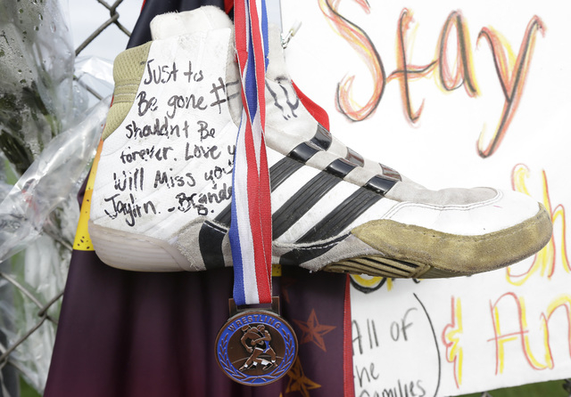A medal and a wrestling shoe with a written message to Jaylen R. Fryberg, 15, is shown as part of a growing memorial at the school, Monday, Oct. 27, 2014 in Marysville, Wash. On Friday, Oct. 24, 2 ...