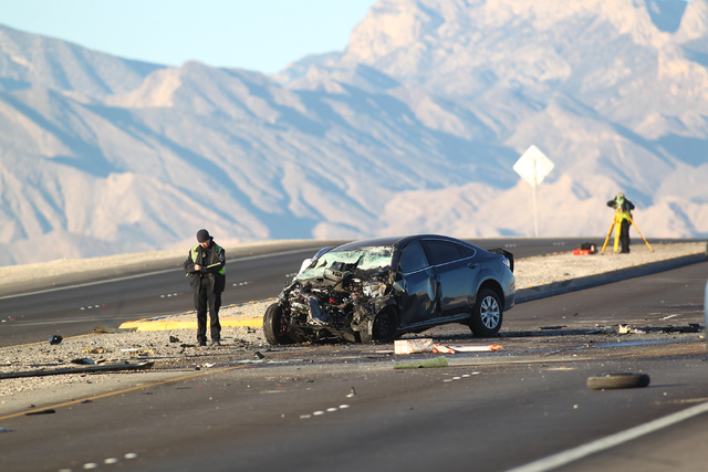 Nevada Highway Patrol officers investigate the scene of a crash involving two vehicles that left three dead near the Fifth Street exit of the 215 Beltway in Las Vegas on Monday morning, Nov. 17, 2 ...