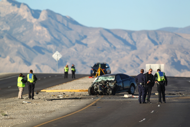 Officials from the Clark County coroner's office and Nevada Highway Patrol officers investigate a crash involving two vehicles that left three dead near the Fifth Street exit of the 215 Beltway in ...