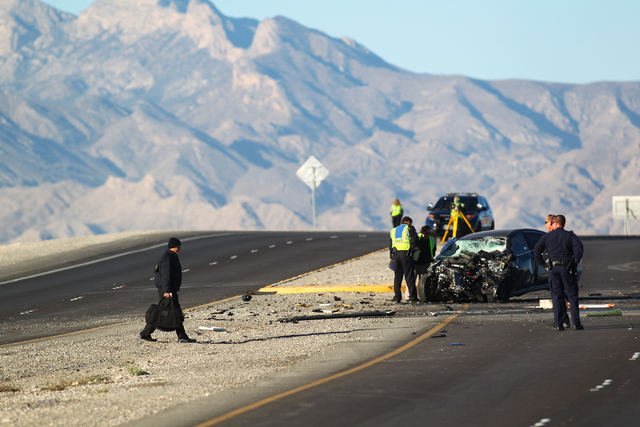 Officials from the Clark County coroner's office arrive at the scene as Nevada Highway Patrol officers investigate a crash involving two vehicles that left three dead near the Fifth Street exit of ...