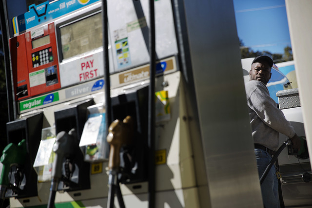 Motorist Jerry Reed watches the pump display while filling up his tank at a gas station, Thursday, Oct. 30, 2014, in Atlanta. The U.S. is on track for the lowest annual average gas price since 201 ...