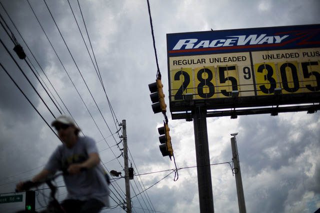 In this Wednesday, Oct. 29, 2014 photo, gas station prices are posted for passing motorists in Augusta, Ga. The U.S. is on track for the lowest annual average gas price since 2010 _ and the 2015 a ...