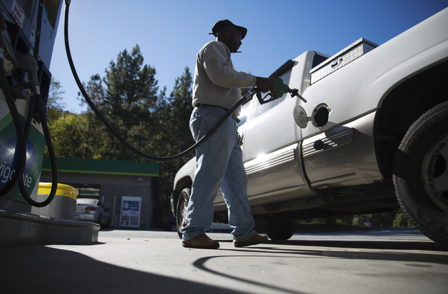 Motorist Jerry Reed fills up his tank at a gas station, Thursday, Oct. 30, 2014, in Atlanta. Almost unbelievably, the national average price of a gallon of gasoline is back under $3 for the first  ...