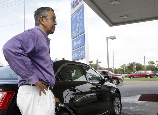 In this Oct. 29, 2014 photo, Mikel Marshall fills his car with gasoline at a Mobil station in Houston, where regular gas was available for $2.85 per gallon. The U.S. is on track for the lowest ann ...