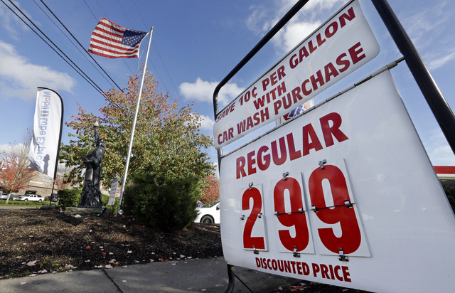In this Wednesday, Oct. 29, 2014 photo, an American flag flies at a gas station advertising a discounted price for gas at $2.99 per gallon, with the purchase of a car wash, in Lynnwood, Wash. The  ...