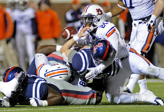 Mississippi quarterback Bo Wallace (14) fumbles the ball while being tackled by Auburn defensive lineman DaVonte Lambert (86) and defensive back Derrick Moncrief (24) during the second half of an  ...
