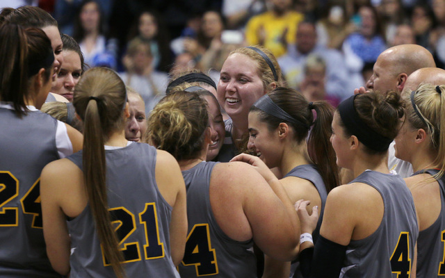 Mount St. Joseph's Lauren Hill, center, gets congratulated by teammates after scoring during her first NCAA college basketball game against Hiram University at Xavier University in Cincinnati on S ...