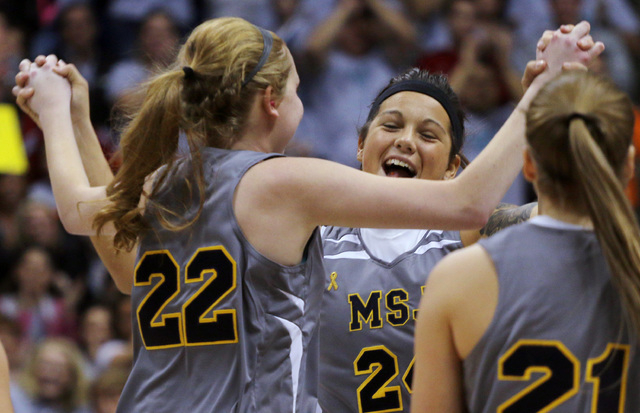Mount St. Joseph's Lauren Hill gets congratulated by teammate Tara Dennis, right, after scoring during her first NCAA college basketball game against Hiram University at Xavier University in Cinci ...