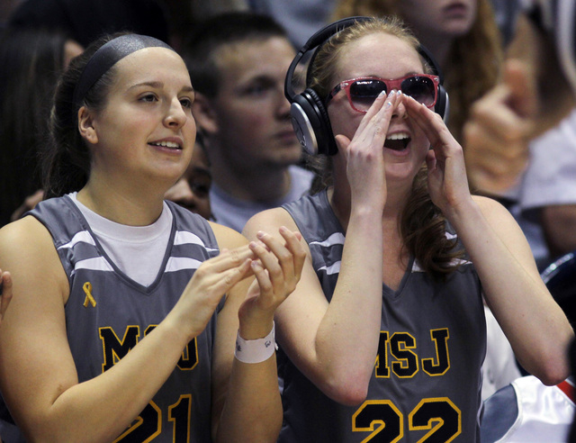 Mount St. Joseph's Lauren Hill, right, cheers on her team with teammate Brooke Mosler during her first NCAA college basketball game against Hiram University at Xavier University in Cincinnati on S ...
