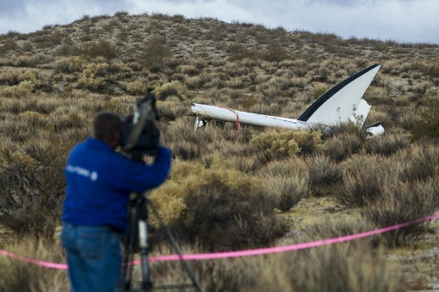 A journalist makes a video of the wreckage near the site where a Virgin Galactic space tourism rocket, SpaceShipTwo, exploded and crashed in Mojave, California, Saturday, Nov 1, 2014. The explosio ...