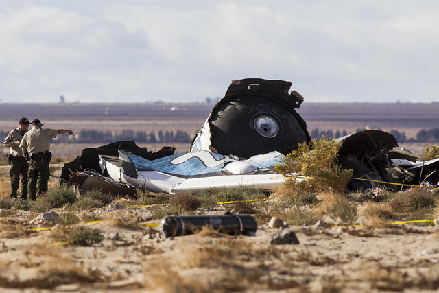 Law enforcement officers take a closer look at the wreckage near the site where a Virgin Galactic space tourism rocket, SpaceShipTwo, exploded and crashed in Mojave, Calif. Saturday, Nov 1, 2014.  ...