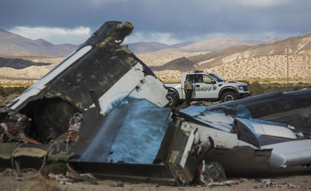 Law enforcement officers keep watch on the wreckage near the site where a Virgin Galactic space tourism rocket, SpaceShipTwo, exploded and crashed in Mojave, Calif. Saturday, Nov 1, 2014. The expl ...