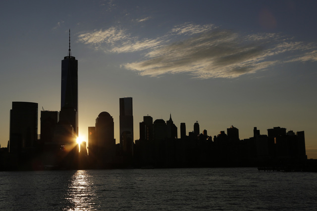 The sun rises next to One World Trade Center, Monday, Nov. 3, 2014 in this view from Jersey City, N.J. Thirteen years after the 9/11 terrorist attack, the resurrected World Trade Center is again o ...
