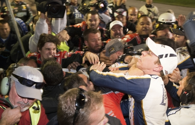 Brad Keselowski, right, is punched during a fight after the NASCAR Sprint Cup Series auto race at Texas Motor Speedway in Fort Worth, Texas, Sunday, Nov. 2, 2014.  The crews of Jeff Gordon and Kes ...