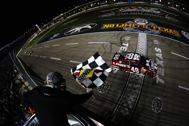 This photo provided by NASCAR shows Jimmie Johnson (48) taking the checkered flag and winning the NASCAR Sprint Cup Series auto race at Texas Motor Speedway in Fort Worth, Texas, Sunday, Nov. 2, 2 ...