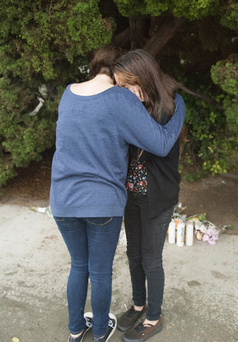 Sandra Anderson, 13, left, and Brianna Diaz, 12, of Orange, California, embrace each other at the street-side memorial at North Jacaranda Street and Fairhaven Avenue in Santa Ana on Saturday, Nov. ...