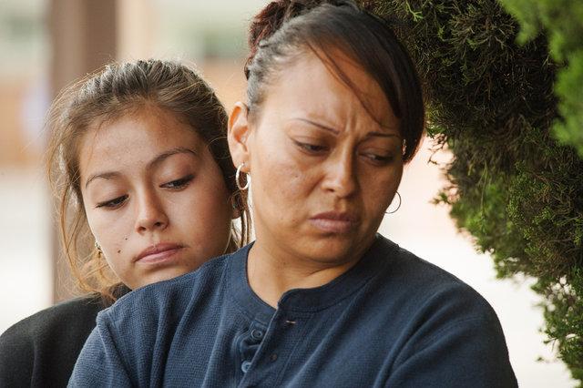 Lindsay Martinez, 14, and her mother, Oralia, of Orange, California, look at the growing street-side memorial at North Jacaranda Street and Fairhaven Avenue in Santa Ana on Saturday, Nov. 1, 2014, ...