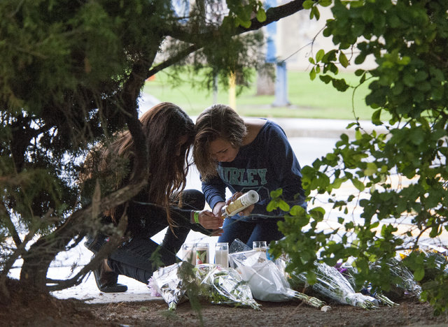 Brianna Diaz, 12, left, and Sandra Anderson, 13, of Orange, California, light a candle at a street-side memorial at North Jacaranda Street and Fairhaven Avenue in Santa Ana on Saturday, Nov. 1, 20 ...