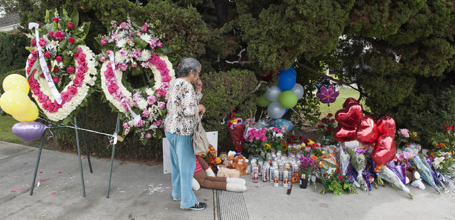 A woman visits the street-side memorial at North Jacaranda Street and Fairhaven Avenue in Santa Ana, California, on Saturday, Nov. 1, 2014, for three teenage trick-or-treaters killed in a Friday n ...