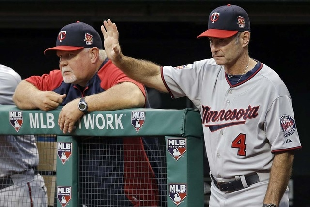 In this Sept. 9, 2014, file photo, Minnesota Twins coach Paul Molitor (4) positions his fielders as he watches from the dugout with manager Ron Gardenhire, left, in the first inning of a baseball  ...