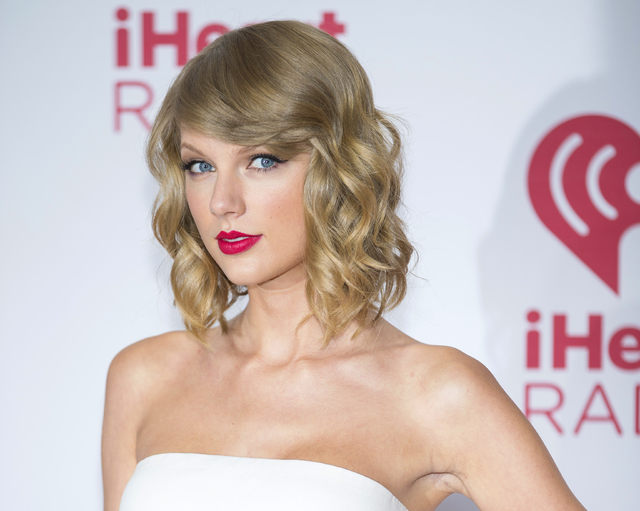 FILE - In this Sept. 19, 2014 file photo, Taylor Swift arrives at the iHeart Radio Music Festival in Las Vegas. The music streaming service Spotify is no longer offering Swift songs at her request ...