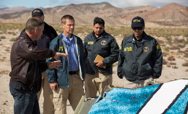 In this Nov. 1, 2014, photo provided by the National Transportation Safety Board, Virgin Galactic pilot Todd Ericson, left, talks with NTSB Acting Chairman Christopher A. Hart, right, at SpaceShip ...