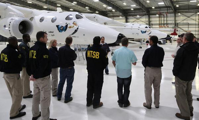 In this Nov. 2, 2014, photo provided by the National Transportation Safety Board, NTSB investigators stands with the WhiteKnightTwo in Virgin Galactic's hangar in Mojave, Calif. The cause of Frida ...