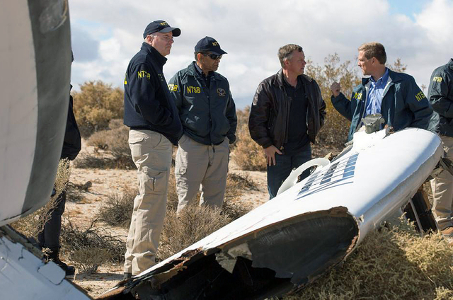 In this Nov. 1, 2014, photo provided by the National Transportation Safety Board, Virgin Galactic pilot Todd Ericson, right, talks with NTSB Acting Chairman Christopher A. Hart, second from left,  ...
