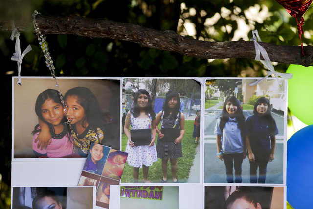 Photographs of twin sisters Lexia, left, and Lexandra Perez are displayed at a makeshift memorial on Monday, Nov. 3, 2014, in Santa Ana, California, near where they and Andrea Gonzales were killed ...