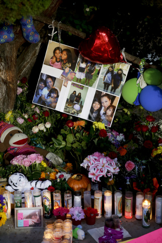 Photographs of twin sisters Lexia  and Lexandra Perez are displayed at a makeshift memorial Monday, Nov. 3, 2014, in Santa Ana, California, near where they and Andrea Gonzales were killed in a hit ...