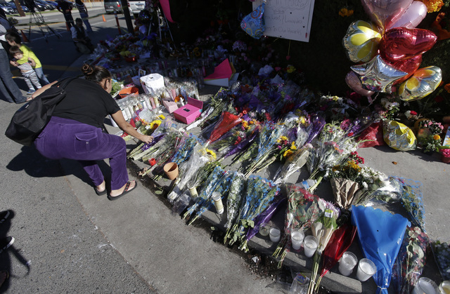 A well-wisher places flowers at a makeshift memorial Monday, Nov. 3, 2014, in Santa Ana, California, near where three teenagers were killed in a hit-and-run accident on Halloween. (AP Photo/Chris  ...