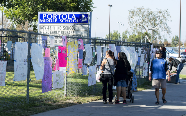 Local residents look thorough the posters on the fence at Portola Middle School created to mourn Portola Middle School students Lexi and Lexandra Perez on Monday, Nov. 3, 2014, in Orange, Californ ...
