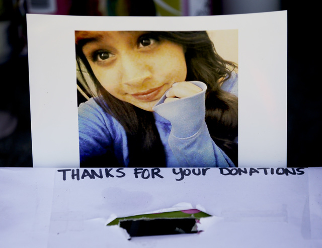 A photograph of Andrea Gonzales is taped to a donation box at a makeshift memorial on Monday, Nov. 3, 2014, in Santa Ana, California, near where Andrea and twins Lexi and Lexandra Perez Huerta wer ...