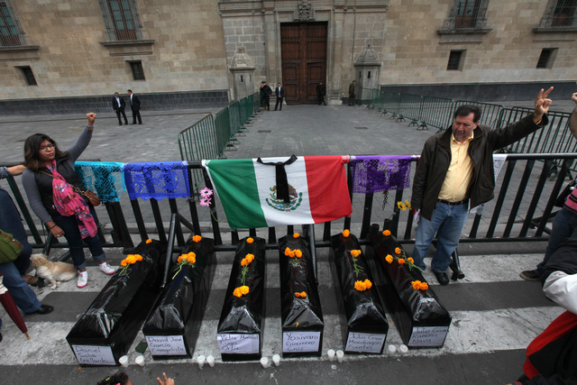 Protesters stand next to six mock coffins, representing those who died in a police attack in Guerrero state, as they demonstrate outside the National Palace in Mexico City, Saturday, Nov. 1, 2014. ...