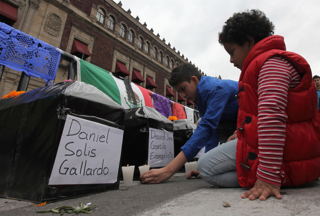 Children place candles next to six mock coffins, representing those who died in a police attack in Guerrero state, placed outside the National Palace by protesters in Mexico City, Saturday, Nov. 1 ...