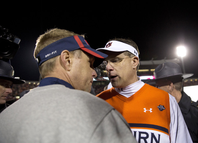 Auburn head coach Gus Malzahn, right, and Mississippi head coach Hugh Freeze meet to shake hands after an NCAA college football game, Saturday, Nov. 1, 2014, in Oxford, Miss. (AP Photo/Brynn Anderson)
