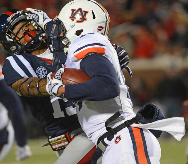 Mississippi defensive back Derrick Jones (19) tackles Auburn quarterback Nick Marshall (14) during an NCAA college football game in Oxford, Miss., Saturday, Nov. 1, 2014. (AP Photo/The Daily Missi ...