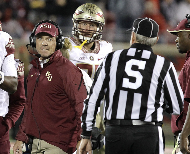 Florida State head coach Jimbo Fisher, left, looks at side judge Watts Key during the second half of their NCAA college football game in Louisville, Ky., Thursday, Oct. 30, 2014.  Florida State de ...
