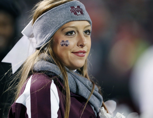 A Mississippi State cheerleader is bundled up for their NCAA college football game against Arkansas in Starkville, Miss., Saturday, Nov. 1, 2014. No. 1 Mississippi State won 17-10. (AP Photo/Rogel ...