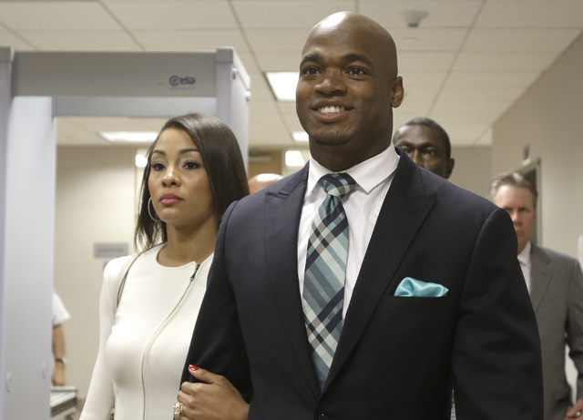 Minnesota Vikings running back Adrian Peterson leaves the courthouse with his wife Ashley Brown Peterson Tuesday, Nov. 4, 2014, in Conroe, Texas. (AP Photo/Pat Sullivan)