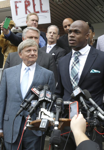 Minnesota Vikings running back Adrian Peterson, right, and his attorney Rusty Hardin, left, speak to the media after pleading no contest to an assault charge Tuesday, Nov. 4, 2014, in Conroe, Texa ...