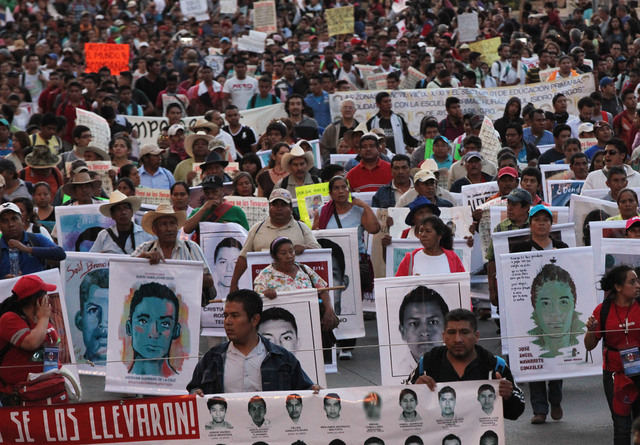 Demonstrators carrying posters of the missing march in protest for the disappearance of 43 students in the state of Guerrero, in Mexico City, Wednesday, Nov. 5, 2014. Federal police detained yeste ...